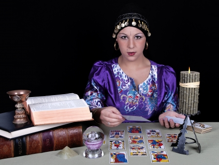 Gypsy fortune teller holding a tarot card