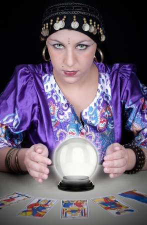 Gypsy fortuneteller uses a crystal ball to foretell the future  Stock Photo