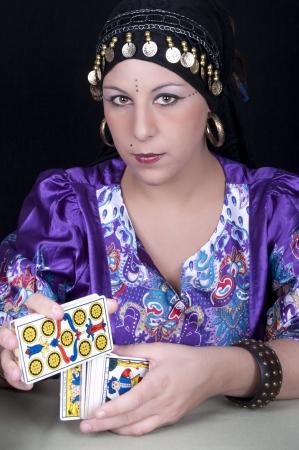 Gypsy Fortune Teller met een tarotkaart Stockfoto