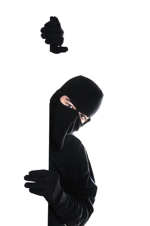 Robber hiding under a wall on white background photo