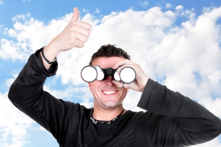 young man with binoculars on blue sky Stock Photo - 15147897