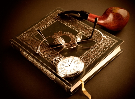 An antique pocket watch, glasses and book photo