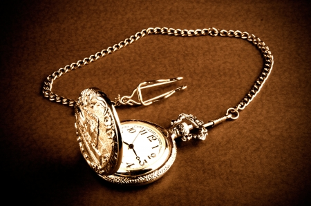 Old retro pocket watch with chain on table  photo