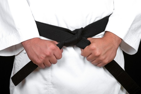 karate man tying the knot to his black belt on black background photo