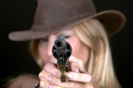 Beautiful cowgirl with a gun on black background photo
