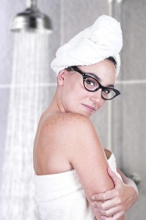 daily routine: linda morena con una toalla de comenzar con su rutina diaria en el ba�o Foto de archivo