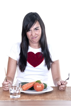 unhappy young beautiful woman keeping a diet and eating vegetables Stock Photo - 15366773
