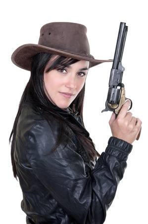Beautiful brunette cowgirl model holding a gun, isolated on white photo