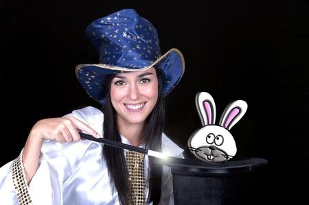 mago: Mujer atractiva con una varita mágica y el sombrero aislado en un fondo blanco sobre Foto de archivo
