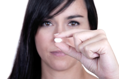 A beautiful woman holding a pill, focus on pill photo