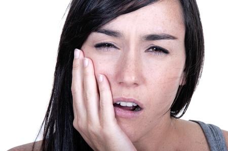 Jonge vrouw in pijn is met kiespijn op wit wordt geïsoleerd
