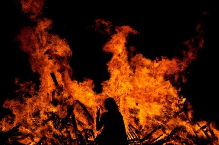 rituales: mujer de pie delante de un gran incendio