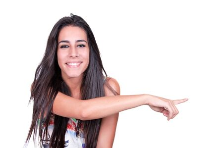 Closeup portrait of a happy young woman pointing at something interesting against white background photo