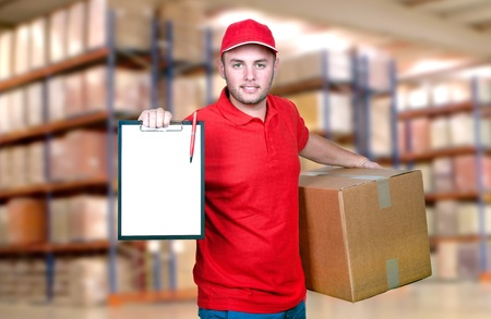 delivery package: Young delivery man in red uniform holding the box