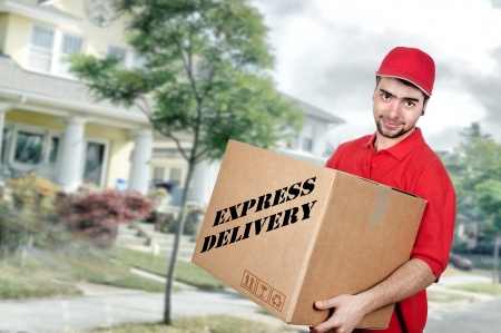 delivery service: Young delivery man in red uniform holding the box