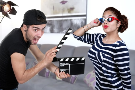 Man Holding Clapper Board And woman actress in studio