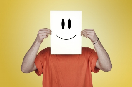 boy showing a blank paper with a happy emoticon in front of his face photo