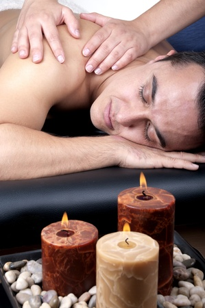 A good-looking man getting a back massage lying down  photo