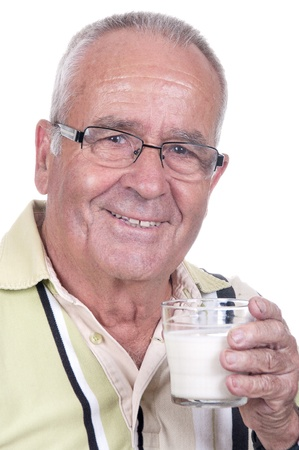 Senior holds happy a glass of milk in hand  photo