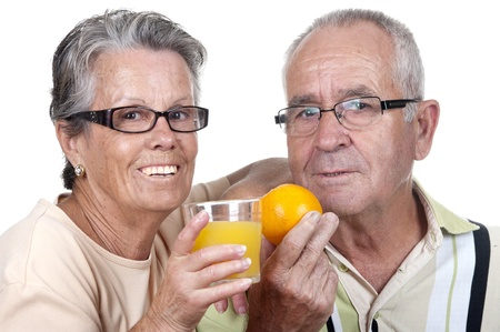 old people eating: old couple holding an orange juice and  one orange, isolated Stock Photo