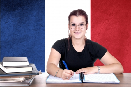 translate: young girl student pc on the background with french national flag. french language learning concept  Stock Photo