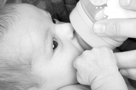 Mother feeding her baby girl with a baby bottle. photo