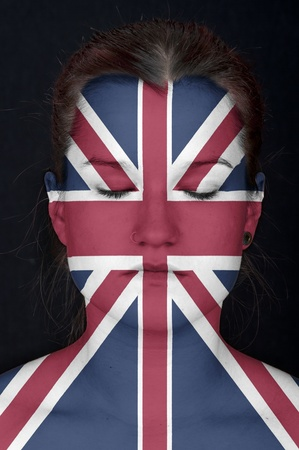 faceart: Portrait of a woman with the flag of the UK painted on her face.  Stock Photo