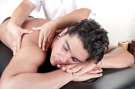 Masseur doing back massage on man body in the spa salon. photo