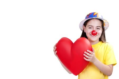 nariz roja: niña vestida como un payaso con un corazón en las manos Foto de archivo