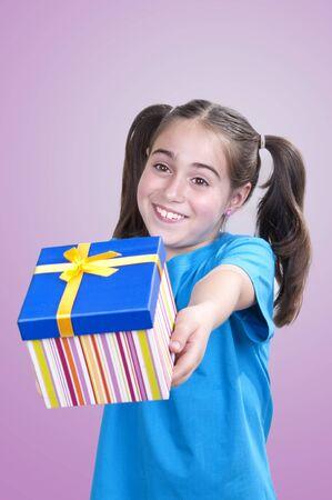 generoso: Feliz niña sonriente celebración y ofreciendo un regalo
