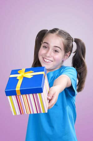 generous: Happy smiling little girl holding and offering a gift