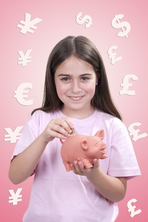 Little girl holding a piggy-bank and inserting a one euro coin  Stock Photo - 21307433
