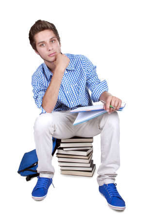 contented: teenage student sitting on a stack of his textbooks on white background Stock Photo
