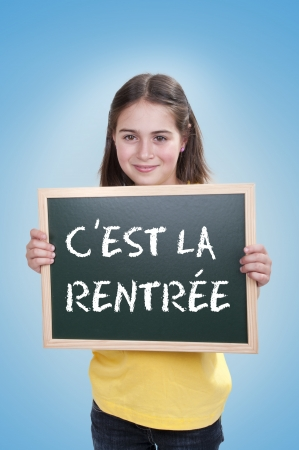 child holding sign: student holding  blackboard  with cest la rentree