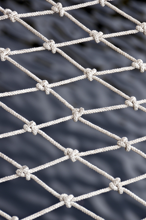 fishnet: Closeup fishnet on sea background.  Stock Photo