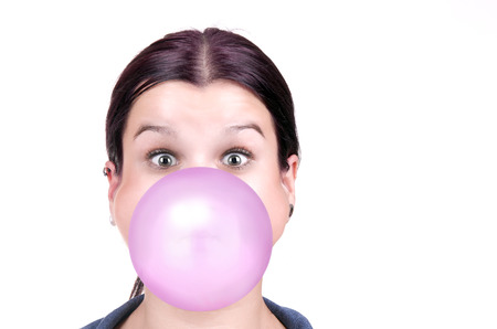 blowing bubbles: young girl with a pink bubble of chewing gum on white background