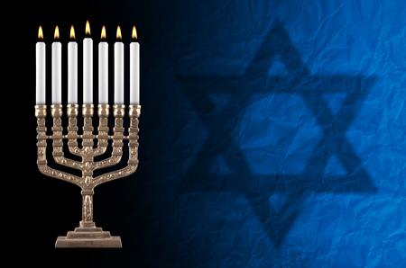 judaical: artisanall lit hanukkah menorah and David star on black background.