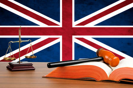 Mallet, legal code and scales of justice with the United Kingdom union jack flag behind.  photo