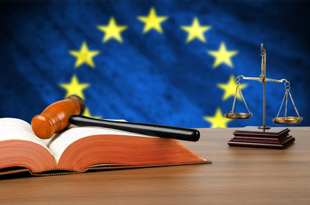 Still life  of a gavel, scales of justice and law book on a judges bench with the European Union flag behind.  photo