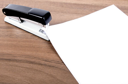 office stapler: sheets of paper stapled by black and grey stapler  Stock Photo