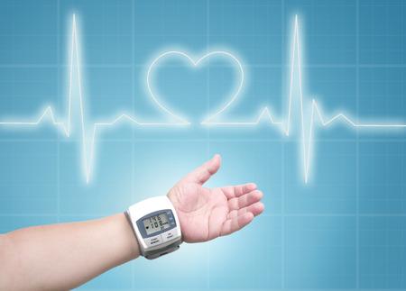 diastolic: blood pressure meter on man wrist, ecg line background