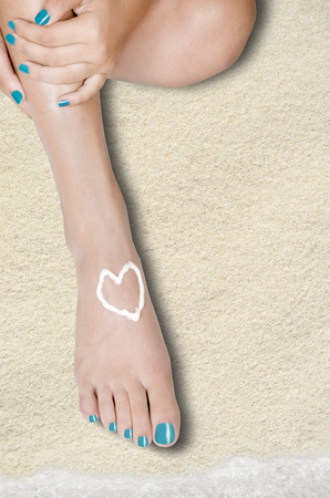 foots: body part shot of beautiful healthy young womans legs. valentines heart is drawn with white care cream on foot