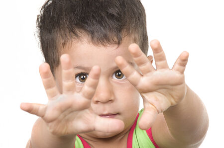 Serious Boy shows Stop hand gesture. Isolated on the White Background  photo