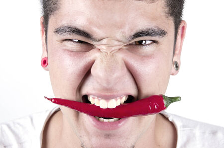 burning man: young man having fun, holding red hot chilly pepper in mouth. Stock Photo