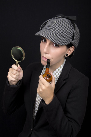 sherlock: Woman as Sherlock Holmes following tracks with magnifying glass Stock Photo