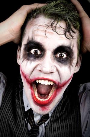 scary clown: Dark creepy joker face screaming angry Stock Photo