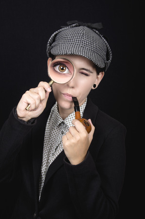 Woman as Sherlock Holmes following tracks with magnifying glass Stock Photo