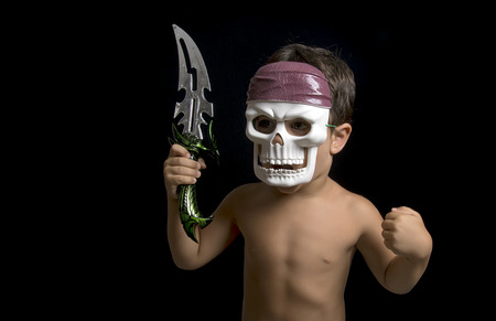 Little boy imitating a warrior with a sword and a mask photo