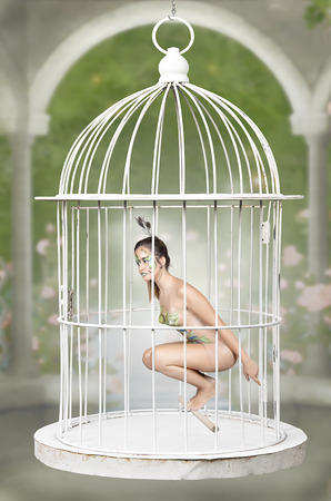 female prisoner: Beautiful girl in a steel cage. Bird dressed Stock Photo