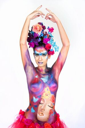body painting: A woman with extreme full-face body painting poses on a white background. Carnival concept
